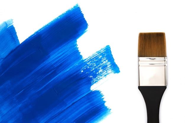 Кисть и мазки синей краской.