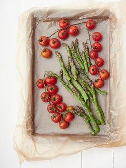 ベーキング羊皮紙、チェリートマト、アスパラガスの野菜のグループ