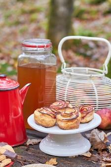 秋のピクニックテーブルのバラの形のリンゴのマフィン、瓶の中の新鮮なリンゴジュース、赤い古いコーヒーメーカー