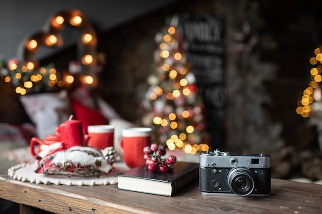 レトロなカメラはクリスマスの歌とクリスマスツリーの背景のテーブルにあります。