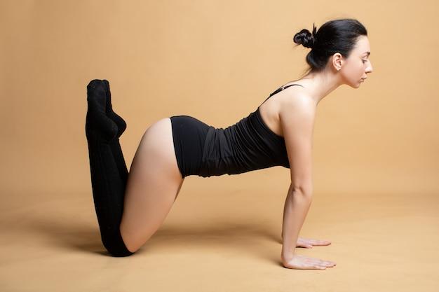Молодая женщина занимается гимнастикой, растяжкой