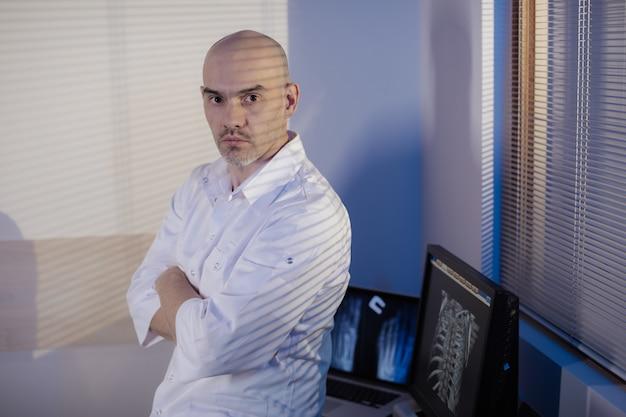 男性医師の写真。医師は断層撮影室に立っています