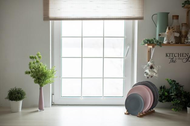 プレートとクリスマス装飾の明るい窓を備えた明るく居心地の良いキッチン