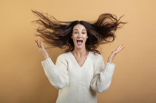 Образ молодой красивой женщины в белом свитере позирует на изолированных оранжевом фоне