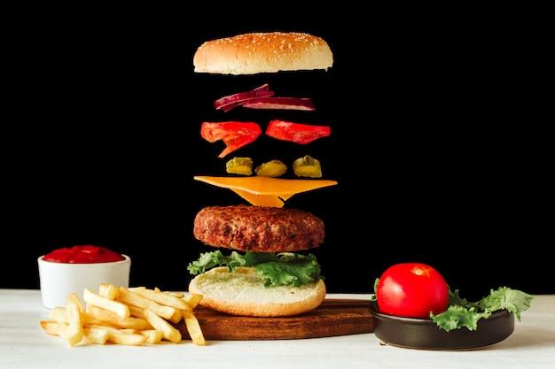 Вкусное мясо на гриле с летающими пищевыми ингредиентами на черно-белом фоне
