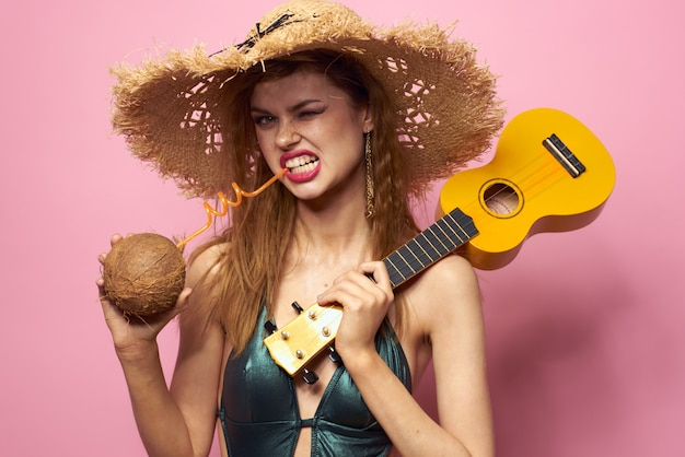Молодая женщина в купальнике и шляпе с ананасом в руке, веселая вечеринка, пляж дома играет на гитаре укулеле