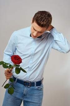 彼の手の中の贈り物として赤いバラを持つハンサムな男の肖像