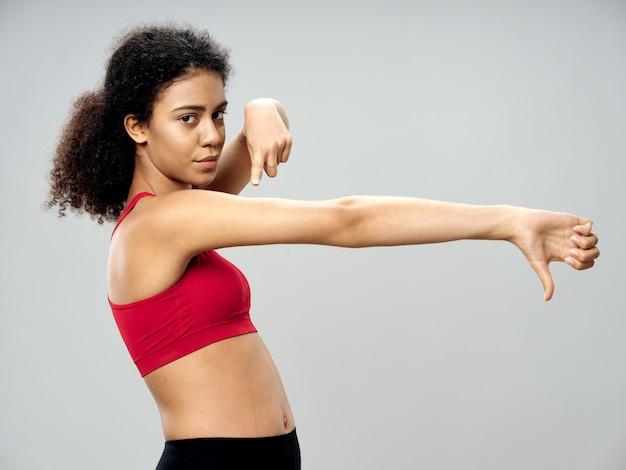 浅黒い肌のアフリカ系アメリカ人女性がトラックスーツでポーズをとってスタジオでスポーツをする