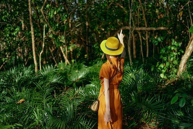 熱帯ジャングルの帽子の若い美しい女性は、自然主義者、公園を散歩します