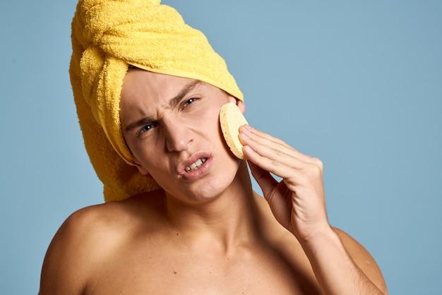 若い男が彼の体と顔の皮膚を気遣って、自宅で顔