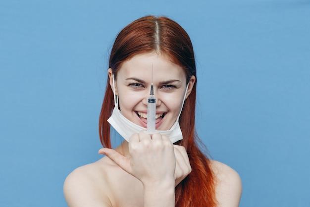 注射器、青いスペースの防護マスクの女性