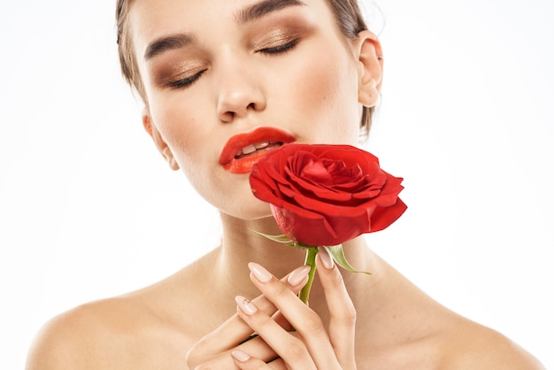 彼女の唇に赤い口紅のあるブルネット、ローズとグラスで美しい女性の肖像画