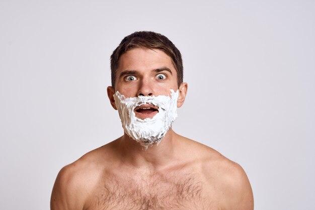 Красивый мужчина бритья с пеной для бритья