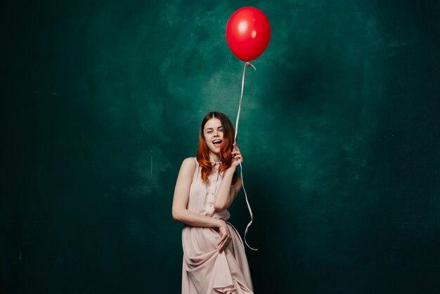 ドレスを着た手に風船を持つ女性