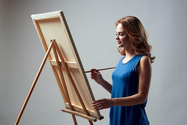 女性アーティストがイーゼルでキャンバスに絵を描く