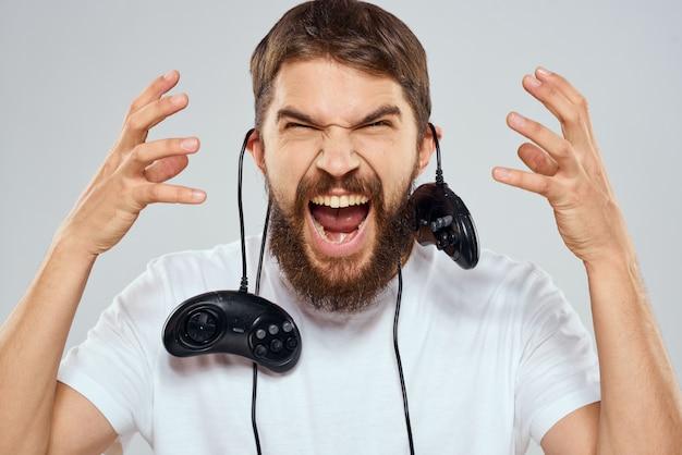 Мужской геймер играет на консоли с джойстиками в наушниках