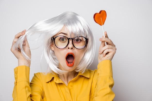 黄色のシャツのテーブルでハートのロリポップと美しい女性モデルは、さまざまな感情をもたらします。バレンタイン・デー