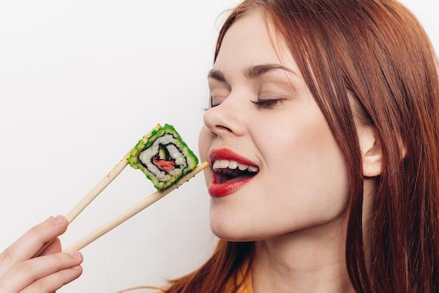 Женщина ест цветные рулетики с бамбуковыми палочками