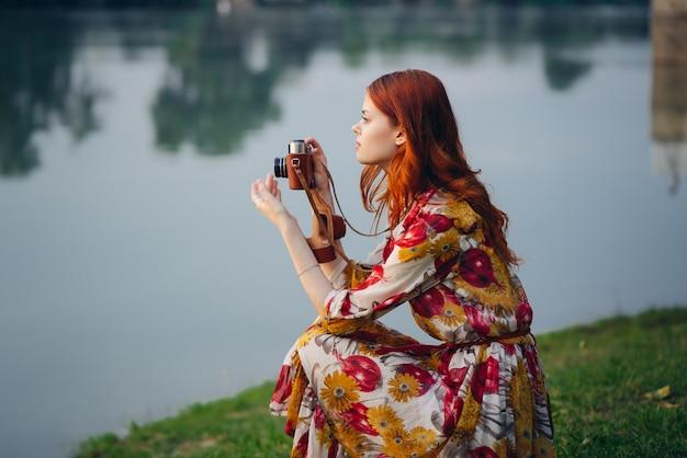 美しい赤髪の女性写真家が古いカメラで写真を撮る