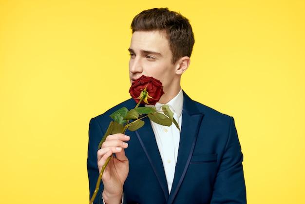 彼の手にバラでセクシーな表情のクラシックなスーツの若い男