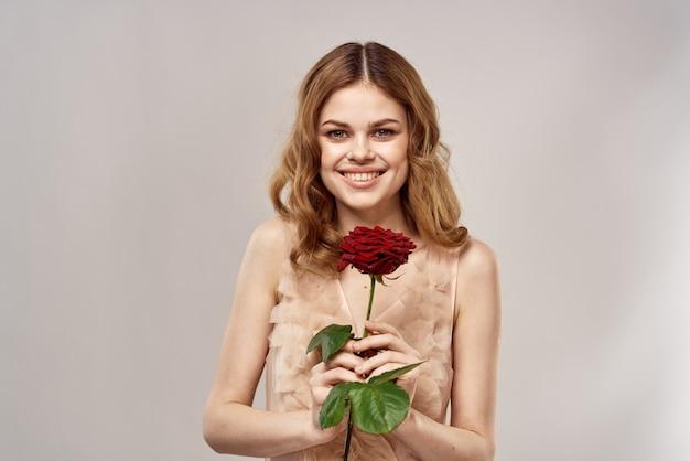 緋色のバラと彼女の手で繊細なドレスの美しい若い女性