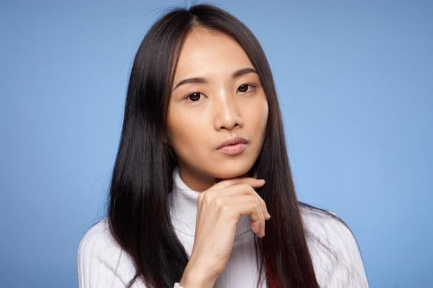 Молодая азиатская женщина на голубой представлять