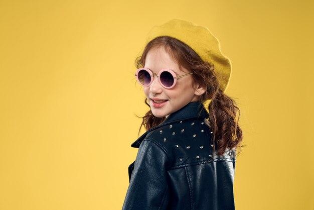 スタイリッシュなイメージと黄色の革のジャケットでポーズ、笑顔の美しい幸せな少女