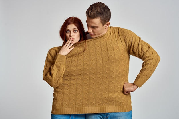 Мужчина и женщина пара позирует в одном свитере, сильная пара влюбленных