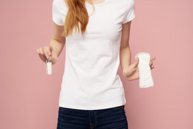 Женщина с прокладкой в руках, гигиеническими прокладками и тампонами, женские дни