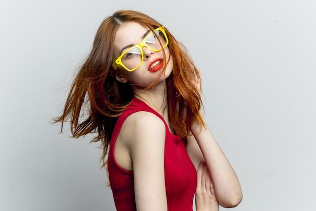 Рыжая женщина в красном платье и желтых очках