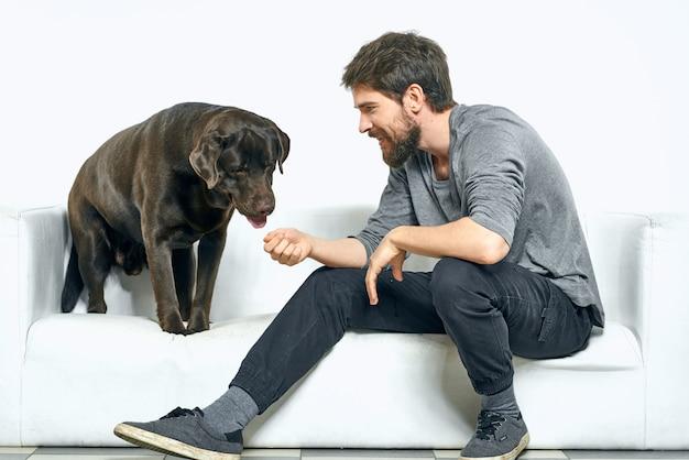 Счастливый человек на диване со своей собакой