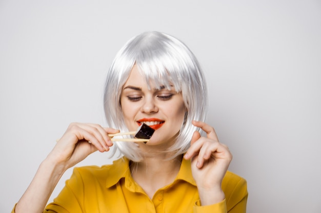 黄色のシャツのポーズでテーブルで寿司と出前からのロールを食べる美人モデル
