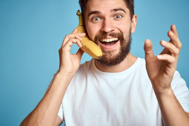 Человек с фруктами в белой футболке на синем