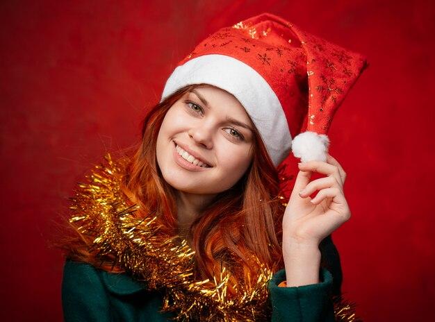 Новогодняя женщина в новогоднем колпаке и мишуре, яркий фон