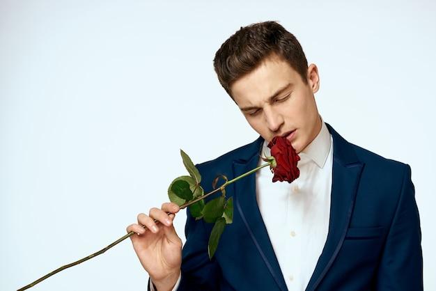 彼の手にバラと古典的なスーツを着たハンサムな男