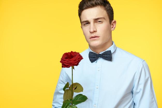 彼の手で美しいバラの花を持つ男