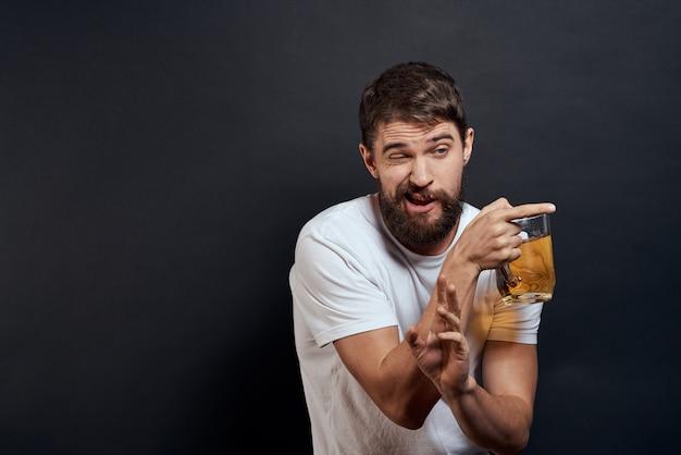 男はグラスからビールを飲み、ジャンクフライのファーストフードを食べる