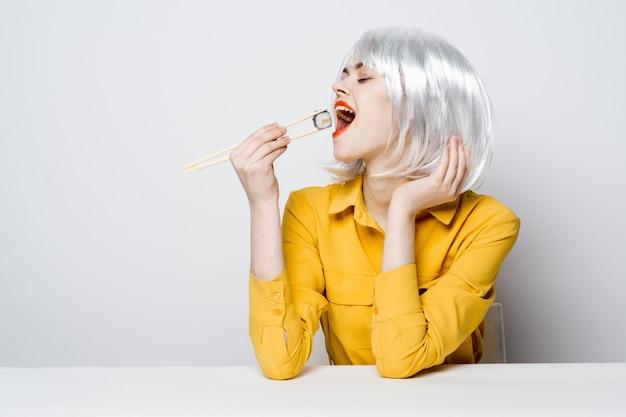 Красивая женщина модель ест суши с палочками для еды