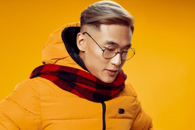 Азиатский мужчина в теплой зимней одежде позирует в студии на цветном фоне