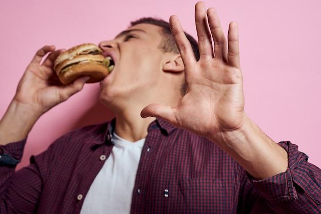 ジャンクフードのトレイを持つ男:ハンバーガーとフライドポテト、ビール