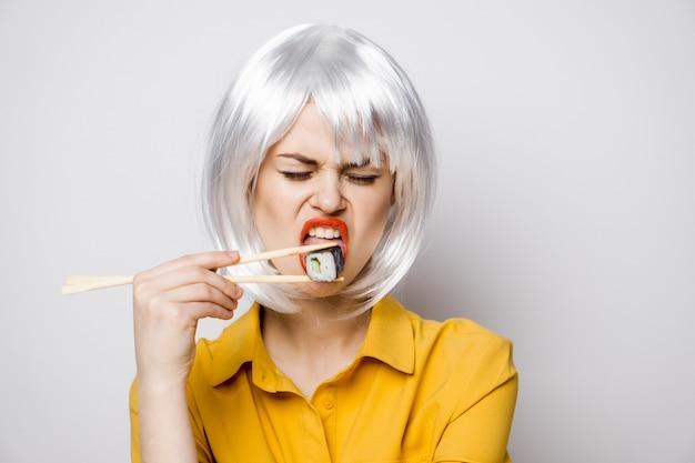Красивая женщина модель ест суши и роллы с доставкой еды за столом в желтой рубашке, создавая разные эмоции