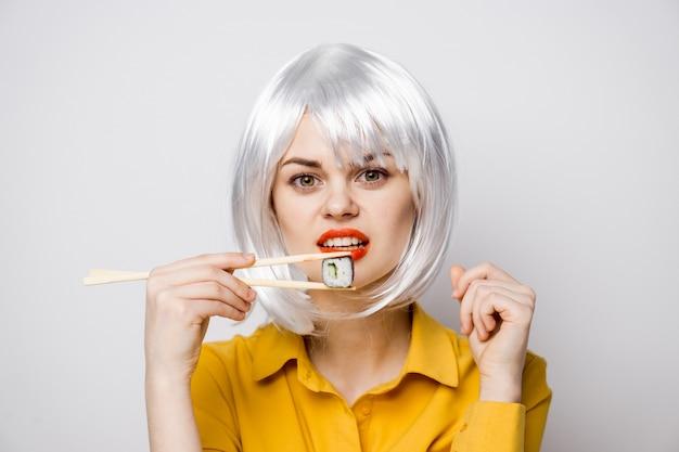 さまざまな感情のポーズをとって黄色のシャツでテーブルで寿司と食糧配達からのロールを食べる美しい女性モデル