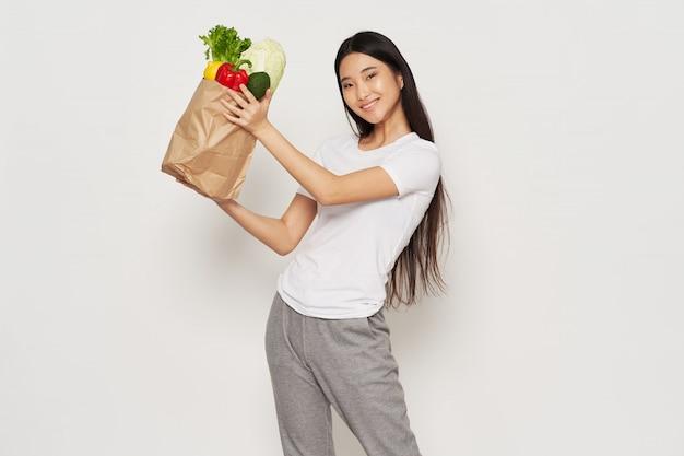 Азиатская молодая красивая женщина с сумкой, полной овощей