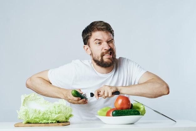 Мужчина сидит за столом с овощами и фруктами, здоровое питание, веганство, вегетарианство