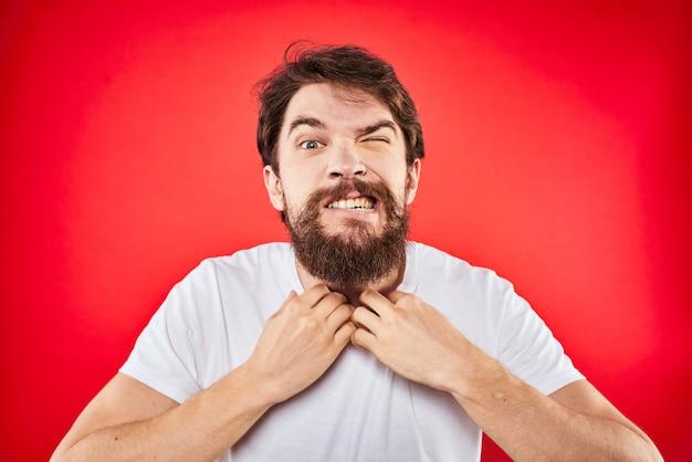 Юноша с бородой в майке демонстрирует разные эмоции, веселье, грусть, злость в студии на стене