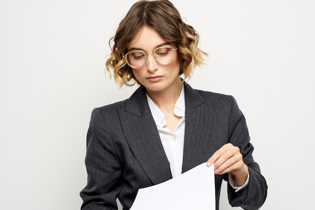 Деловая женщина в костюме и очках позирует в студии, светлые стены