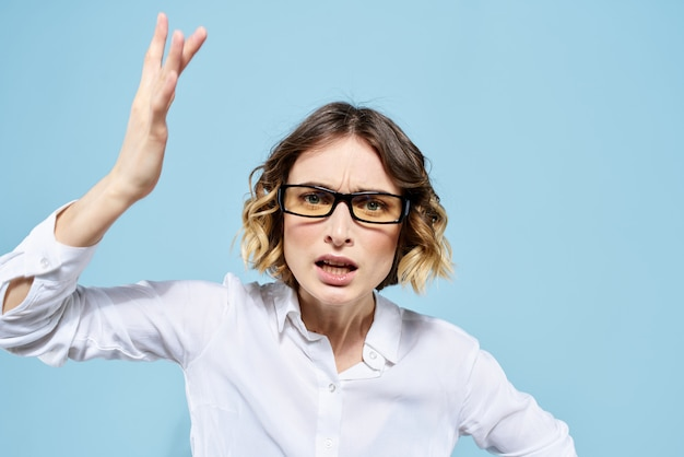 Деловая женщина в белой рубашке и очках позирует в студии, светлые стены