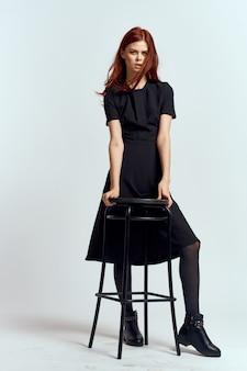光の壁でポーズ黒いドレスの女性モデル