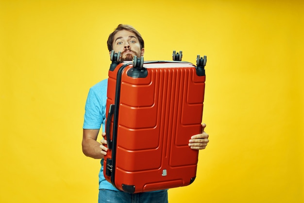 彼の手のポーズでスーツケースを持つ男性旅行者