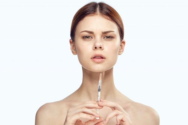 Молодая девушка со шприцем для инъекций в кожу, уколы красоты